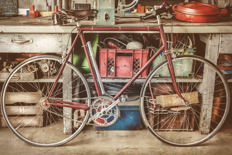 Tävlings- bycicle för tappning framme av en gammal arbetsbänk med hjälpmedel arkivbilder