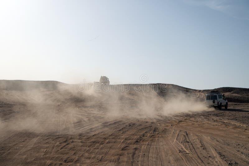 Tävlings- utmaningöken för konkurrens För sanddyn för bil betagna hinder Bilen kör offroad med Offroad moln av damm arkivfoto