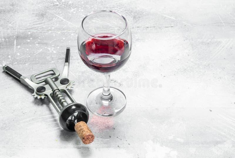 tła szkła czerwone wino Czerwone wino z corkscrew fotografia stock