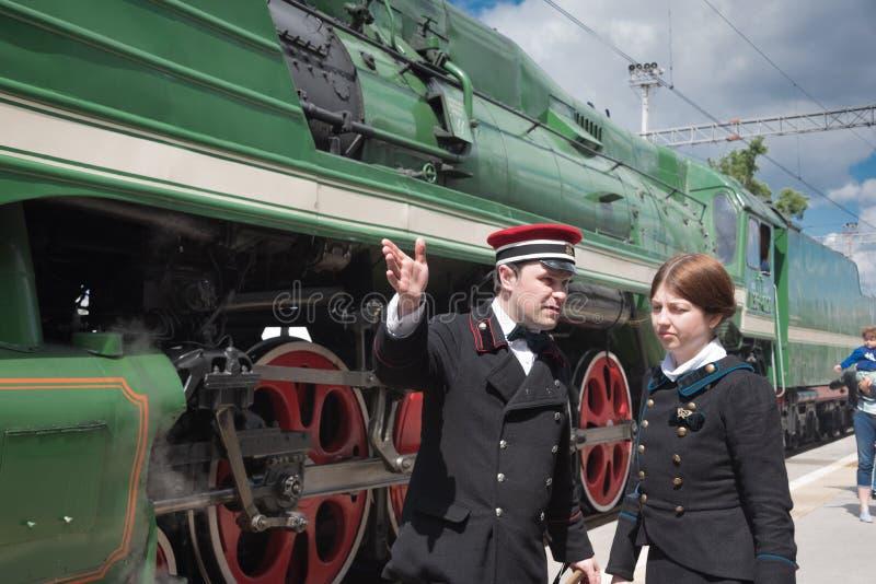 Tågledare på järnvägsplattformen Rizhsky på bakgrunden av ånglokomotivet med röda hjul. royaltyfri foto
