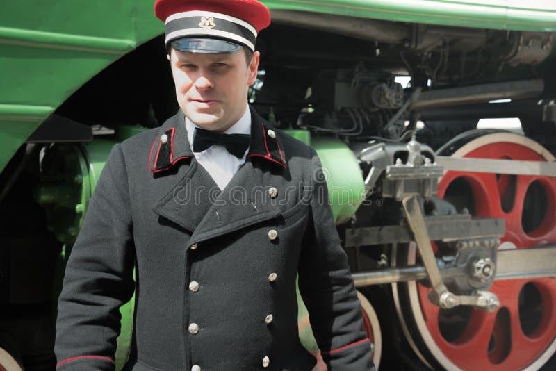 Tågledare på järnvägsplattformen Rizhsky på bakgrunden av det gröna ånglokomotivet med röda hjul. arkivbilder