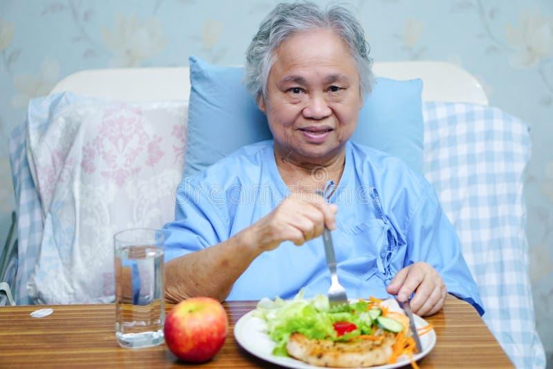 Tålmodig ätafrukost för asiatisk pensionär eller för äldre kvinna för gammal dam arkivbild