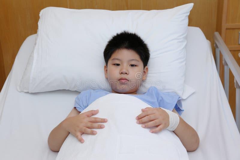 Tålmodig dräkt för pojkekläder i sjukhussäng arkivbild