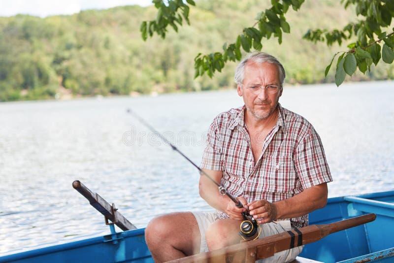 Tålmodig hög man i fartyget, medan fiska royaltyfri foto