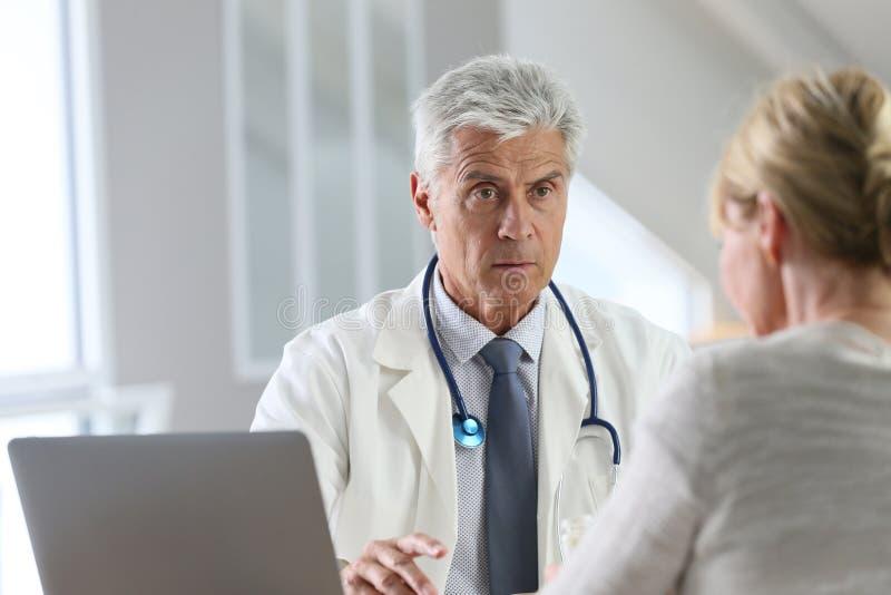 Tålmodig konsulterande doktor på hans kontor arkivfoto