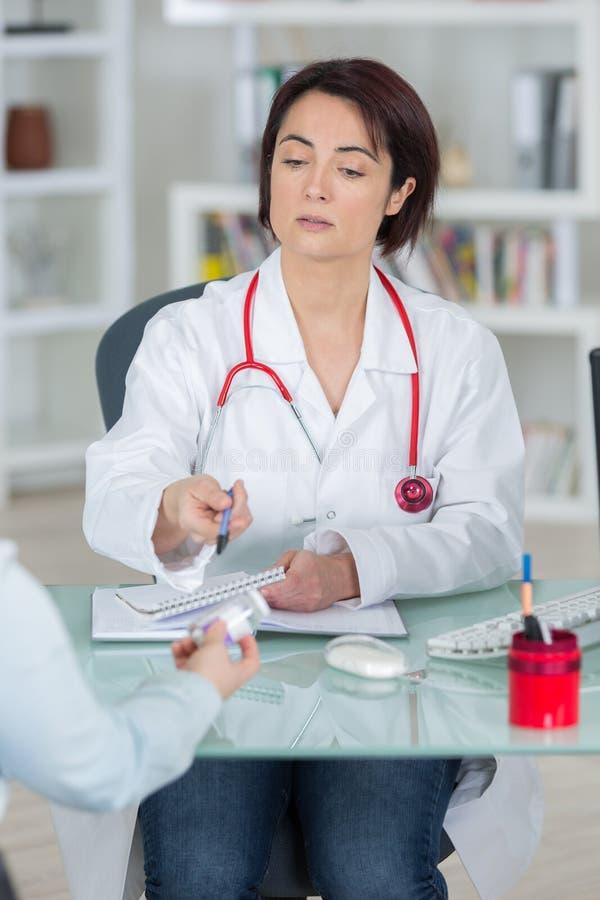 Tålmodig läkarbehandling för mogen kvinnlig doktorsvisning i regeringsställning royaltyfri foto