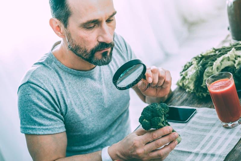 Tålmodig lugna man som studerar olika gröna grönsaker royaltyfri bild