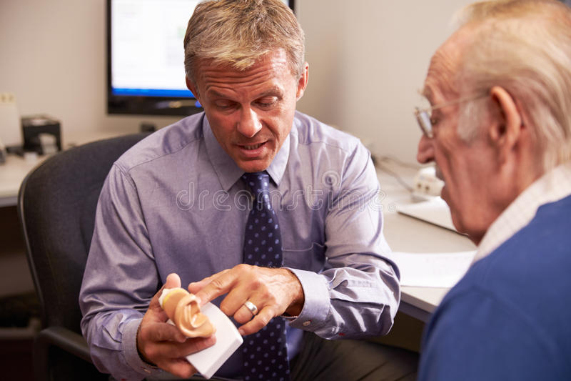 Tålmodig modell Of Human Ear för doktor Showing Senior Male royaltyfria bilder