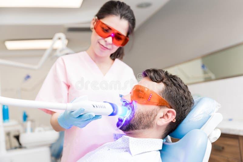 Tålmodig mottagande tand- behandling från tandläkare arkivfoton