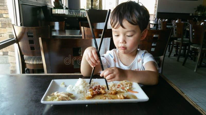 Tålmodig ung kines- och Caucasianpojke som lär att använda pinnar arkivbild