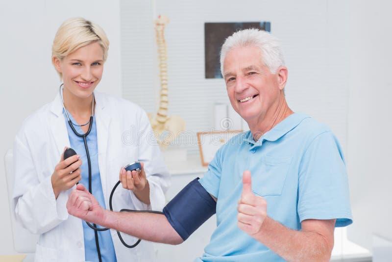 Tålmodiga visningtummar upp medan doktor som kontrollerar hans blodtryck royaltyfria foton