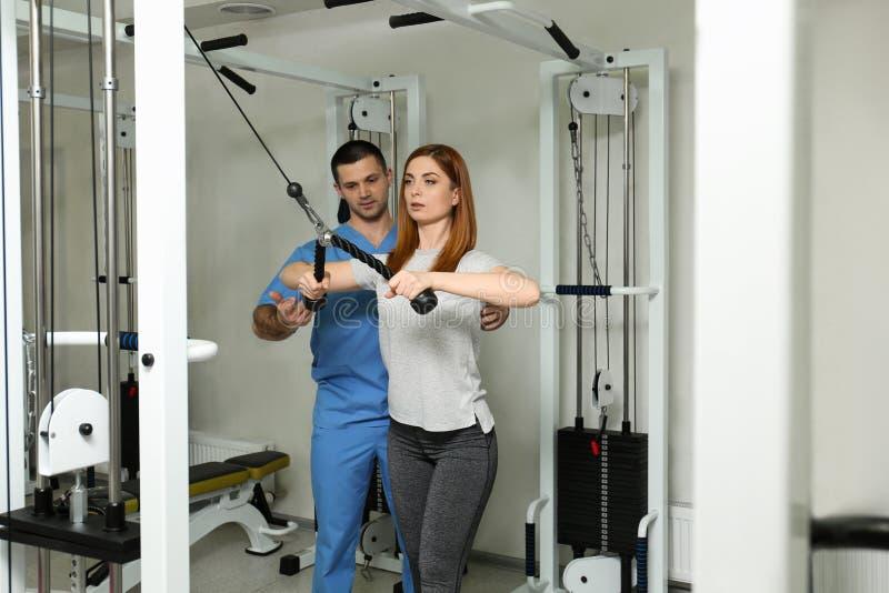 Tålmodigt öva under fysioterapeutövervakning royaltyfri fotografi