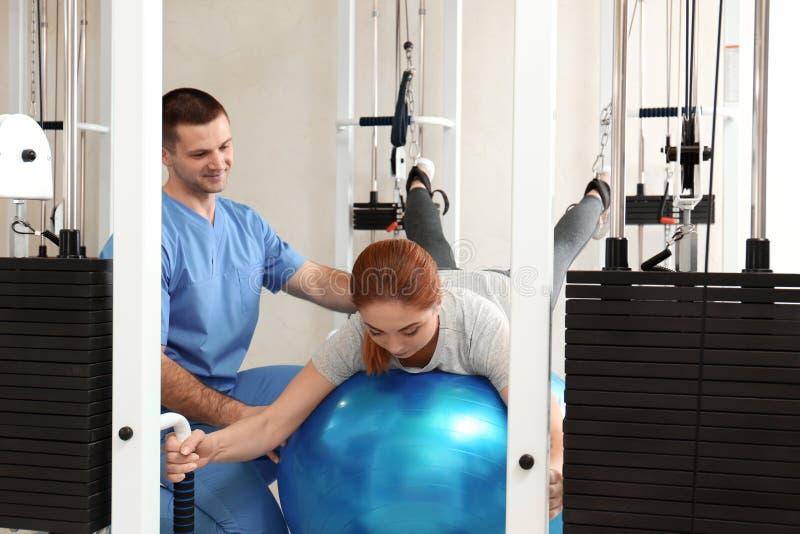 Tålmodigt öva under fysioterapeutövervakning royaltyfria foton