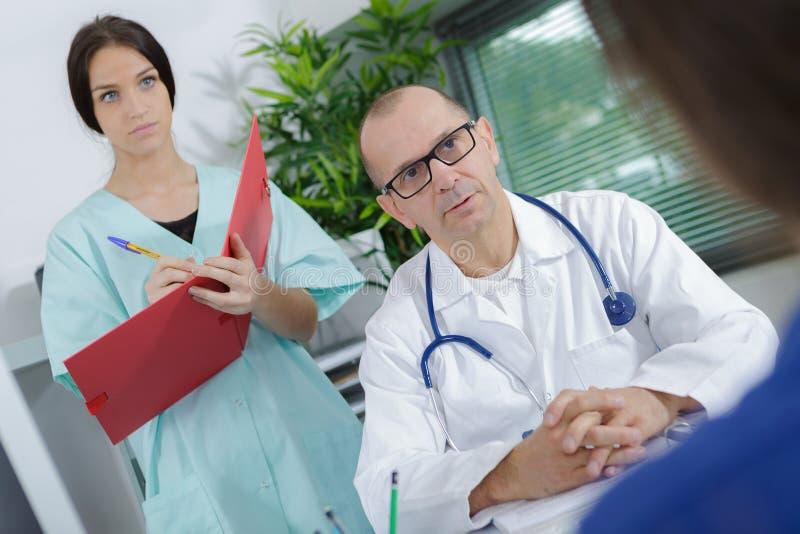 Tålmodigt ha konsultation med sjuksköterskahandstilanmärkningar i regeringsställning royaltyfri fotografi