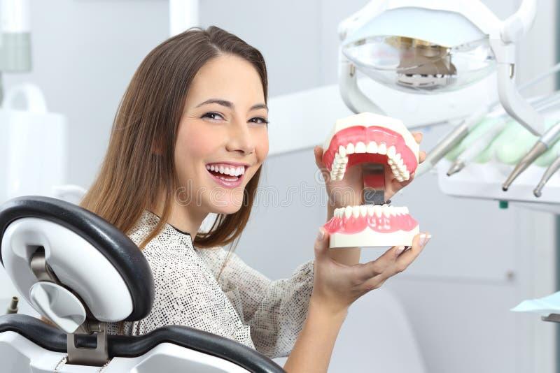 Tålmodigt le för tandläkare med en plast- tandprotes arkivfoto