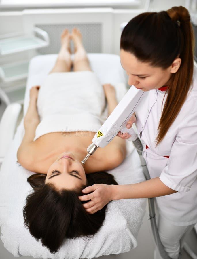 Tålmodigt ligger på soffan, medan doktor-kosmetologen utför ett kosmetiskt tillvägagångssätt på hennes framsida med medicinsk las arkivbild