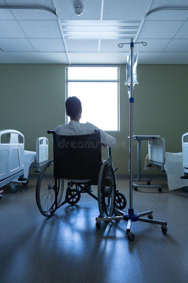 Tålmodigt se till och med fönster, medan sitta i rullstol i sjukhus arkivfoto