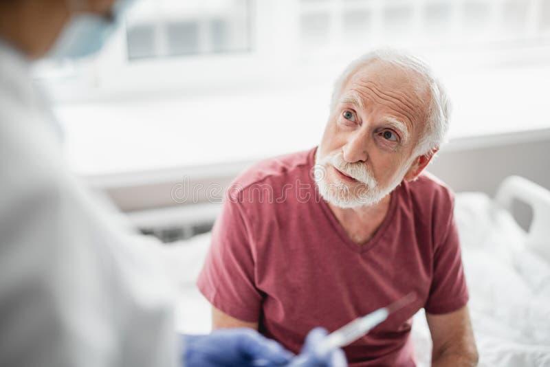 Tålmodigt sitta på sjukhussäng och se doktorn fotografering för bildbyråer