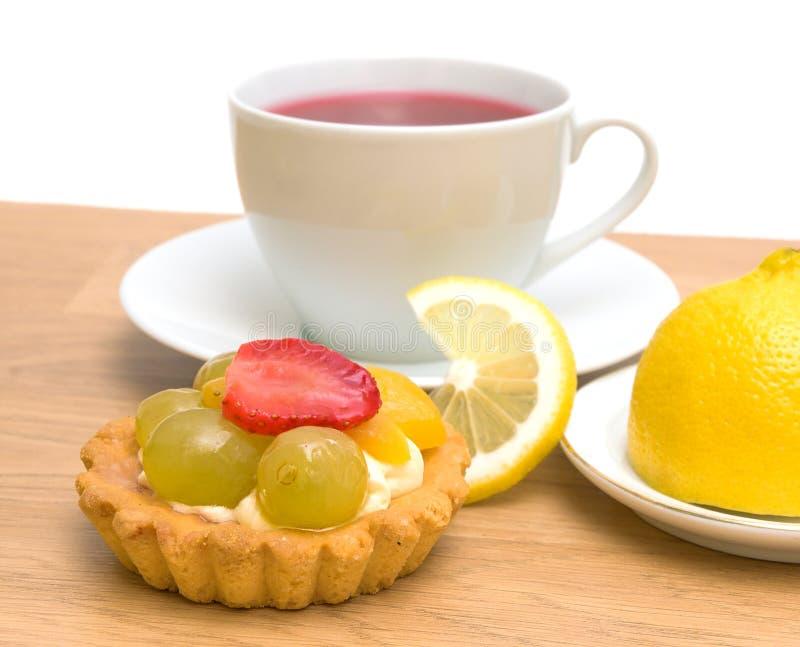 Tårta, citron och en kupa av frukttea på en vitbakgrund arkivfoton