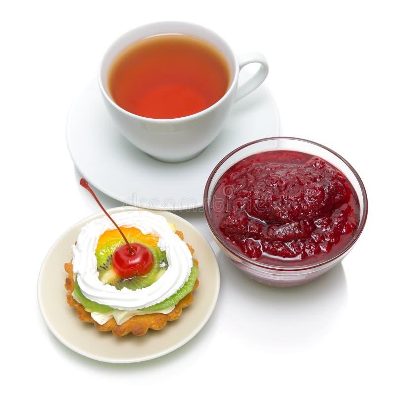 Tårta, driftstopp och en kupa av tea på en vitbakgrund royaltyfria bilder