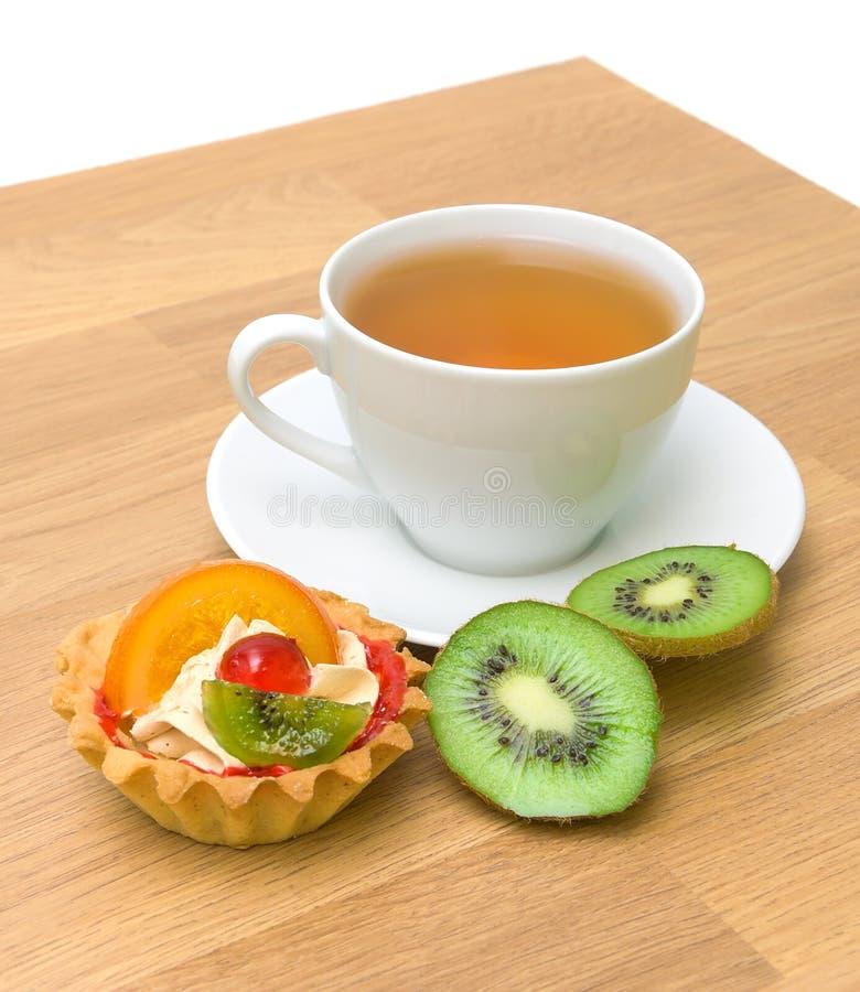 Tårta, kiwi och en kupa av tea royaltyfria foton