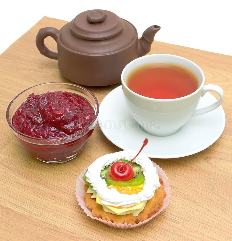 Tårta med frukt, cranberrydriftstopp och en kupa av tea royaltyfri bild