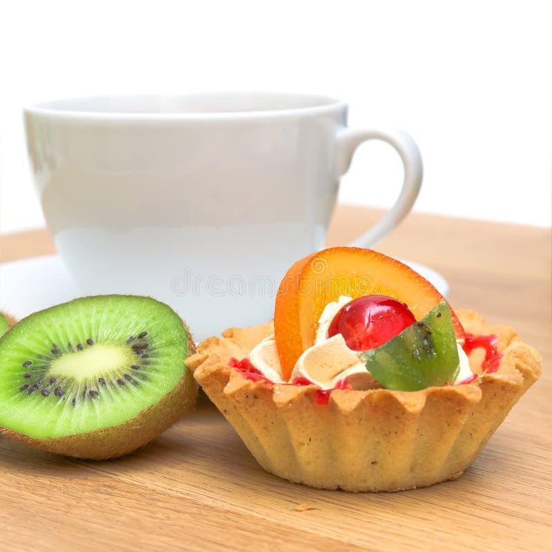 Tårta med frukt, kiwi och en kupa av tea arkivbilder