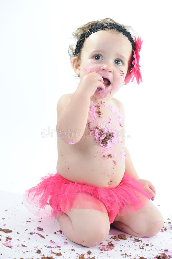Tårtadundersuccéfor: Smutsigt behandla som ett barn flickan som äter födelsedagtårtan! royaltyfri foto