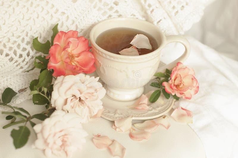 Tè aromatico in una tazza d'annata e le rose rosa, i colore pastello della prima colazione deliziosa e bella fotografie stock libere da diritti
