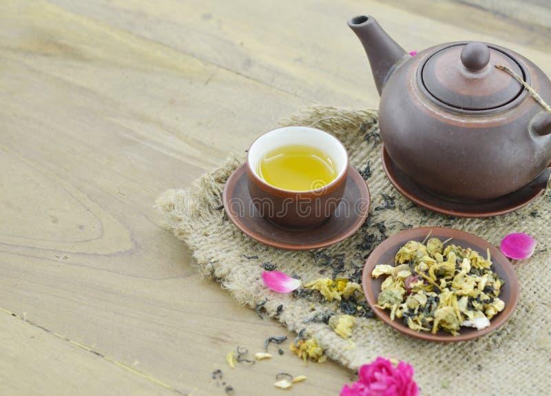 Tè asciutto in piatto con tè in tazza e teiera su fondo di legno fotografie stock