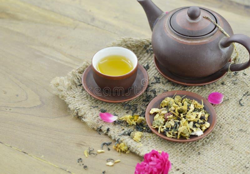Tè asciutto in piatto e tè in tazza e teiera sulla tavola di legno immagine stock