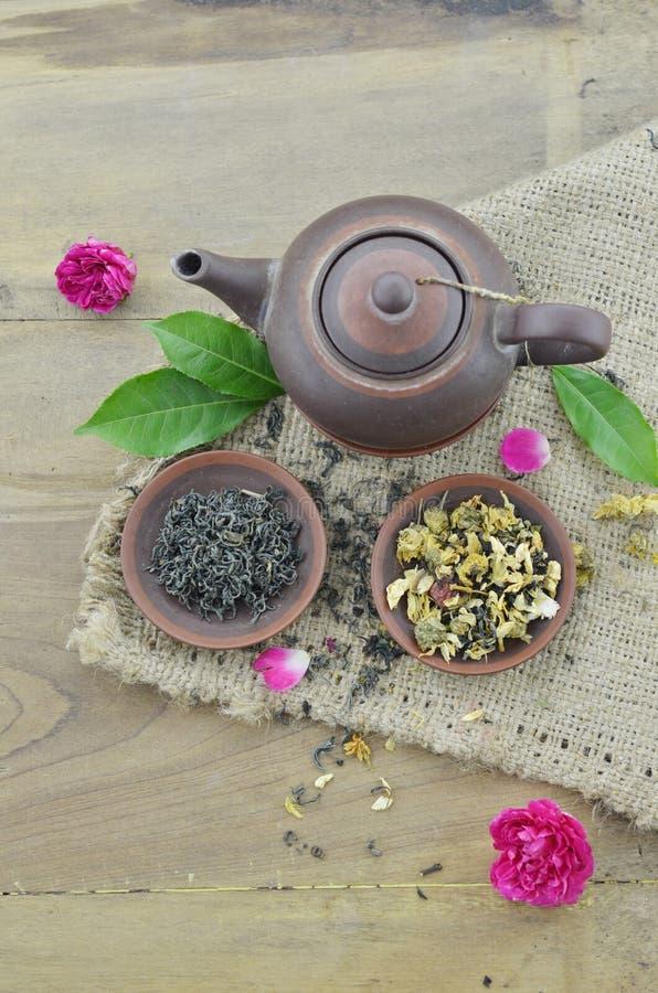 Tè asciutto in piatto e teiera su fondo di legno immagine stock libera da diritti