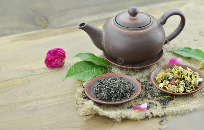 Tè asciutto in piatto e teiera su fondo di legno fotografia stock