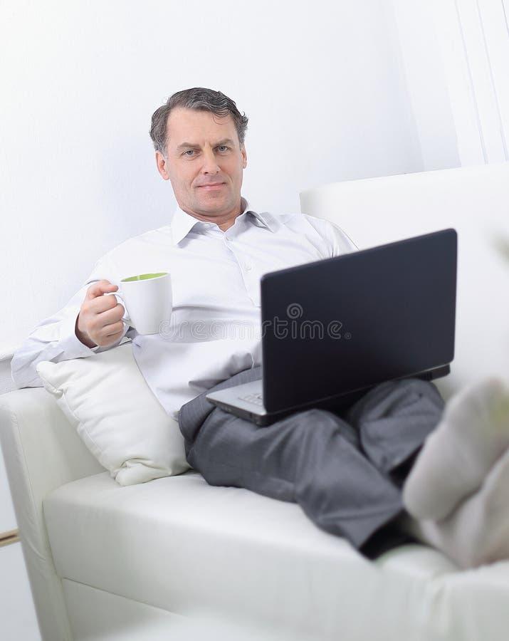 Tè bevente dell'uomo d'affari e lavorare al computer portatile nella camera di albergo immagini stock libere da diritti