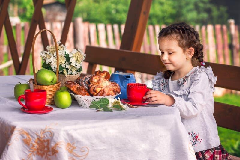 Tè bevente della bambina con i panini fotografia stock