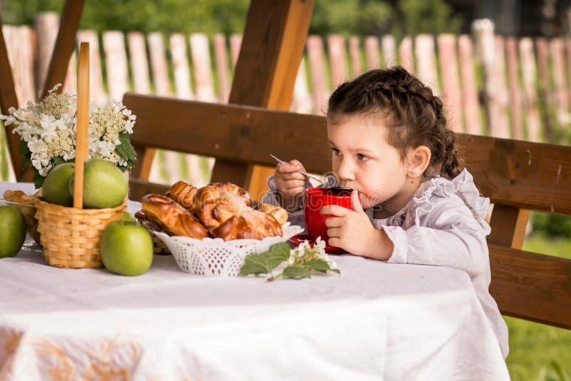 Tè bevente della bambina con i panini fotografie stock libere da diritti