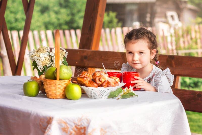 Tè bevente della bambina con i panini fotografia stock libera da diritti