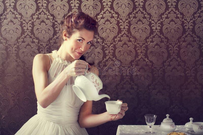 Tè bevente della donna del sognatore a tempo del tè immagine stock
