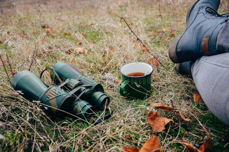 Tè bevente della giovane donna su una natura di autunno Binoculare, viaggiatore immagini stock libere da diritti