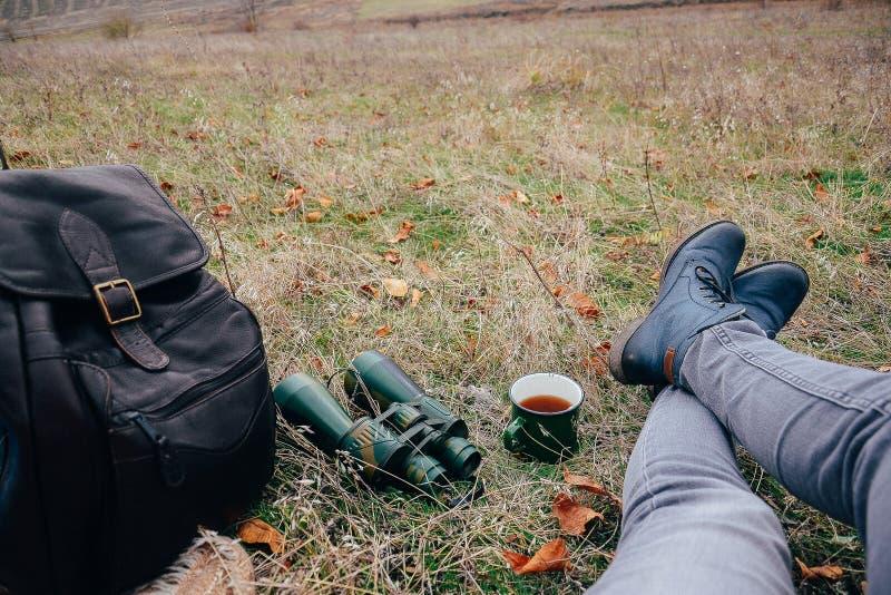 Tè bevente della giovane donna su una natura di autunno Binoculare, viaggiatore immagini stock