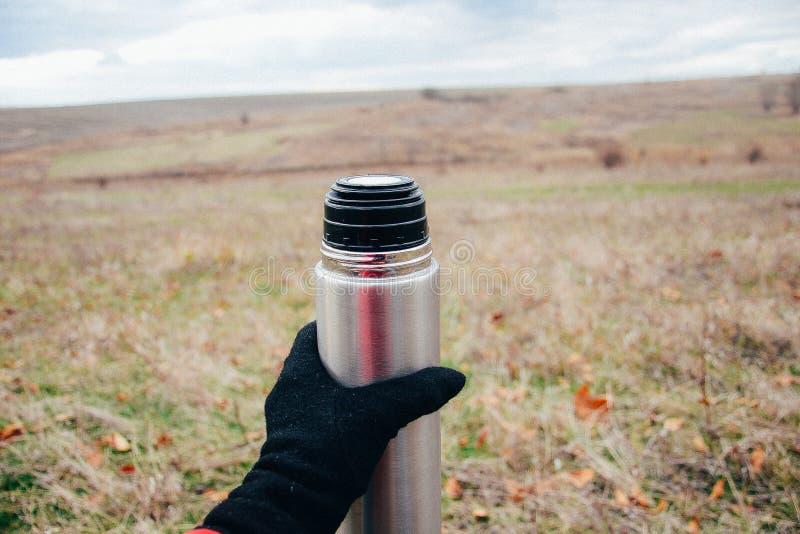 Tè bevente della giovane donna su una natura di autunno Binoculare, viaggiatore fotografia stock libera da diritti