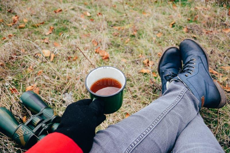 Tè bevente della giovane donna su una natura di autunno Binoculare, viaggiatore immagine stock