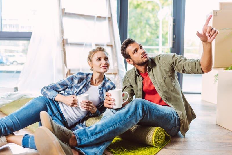 Tè bevente delle coppie in nuovo appartamento immagine stock libera da diritti