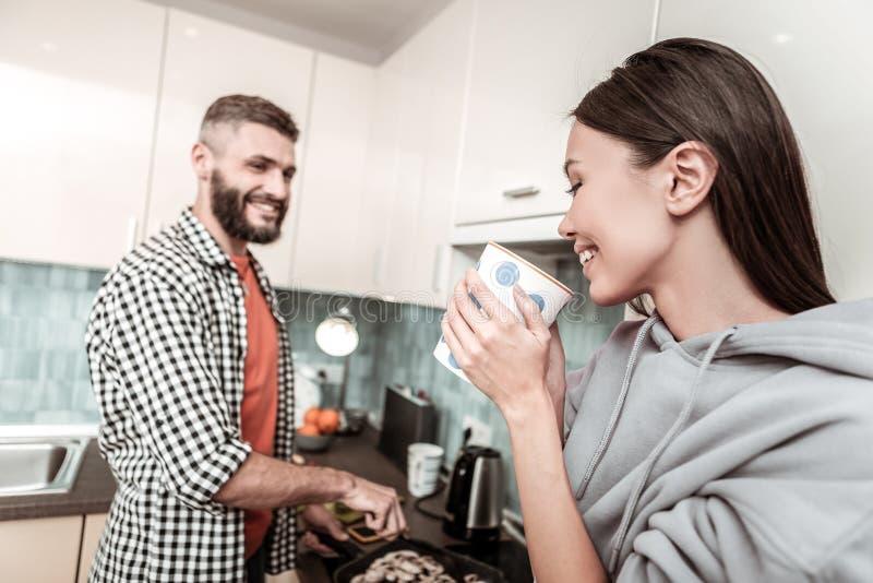 Tè bevente sorridente della donna mentre guardando la sua cottura dell'uomo fotografia stock