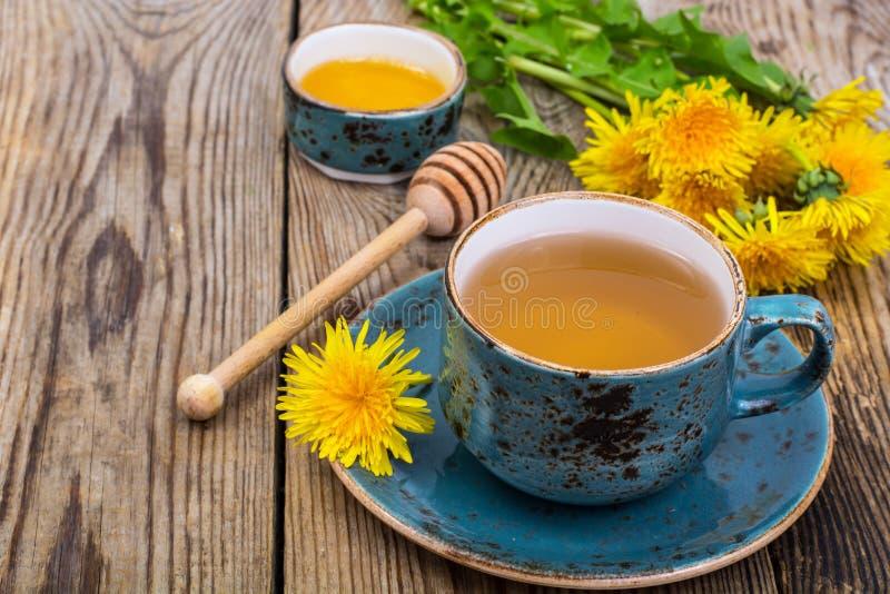 Tè caldo e miele fragrante dai denti di leone in una tazza d'annata blu fotografie stock libere da diritti