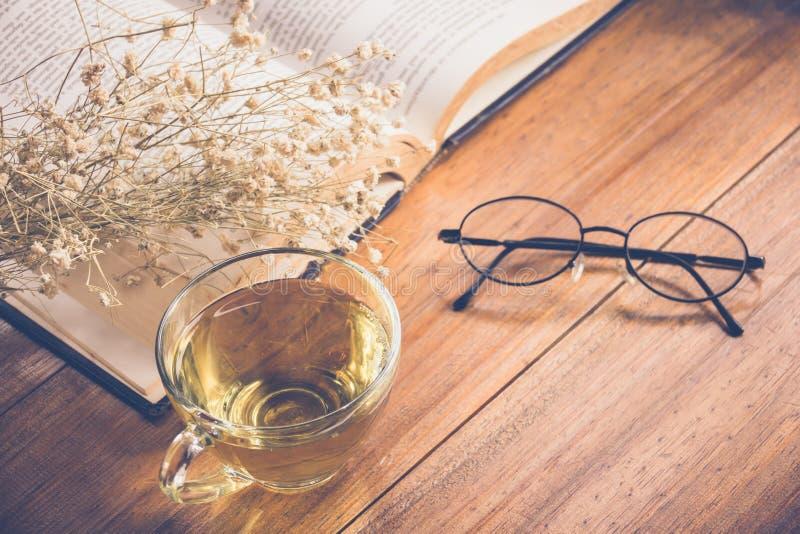 Tè caldo in una tazza con i vetri di lettura sul vecchio libro e sul fiore sopra immagine stock libera da diritti