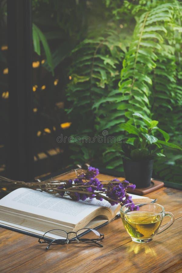 Tè caldo in una tazza con il vecchio libro ed il fiore sulla tavola immagine stock libera da diritti