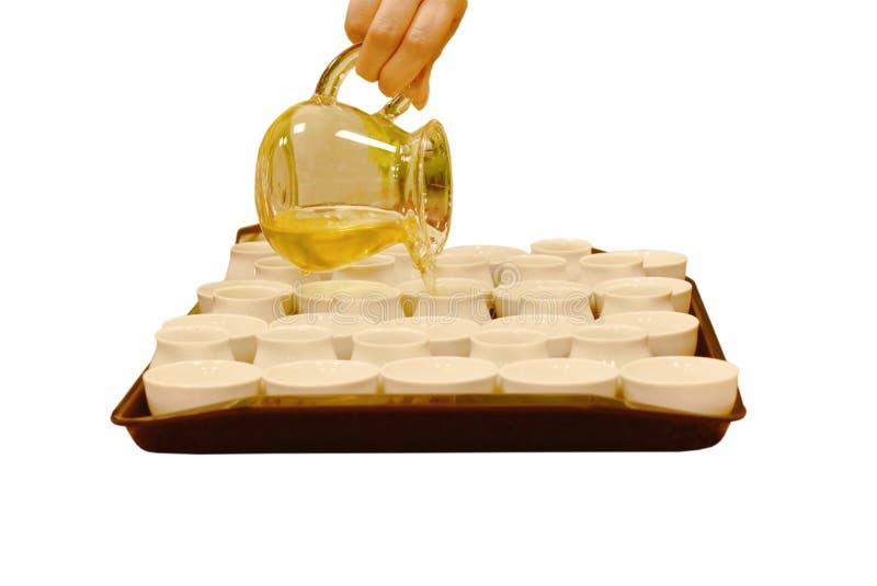 Tè cinese caldo fatto a mano e versare dal barattolo per foggiare a coppa su fondo bianco fotografia stock
