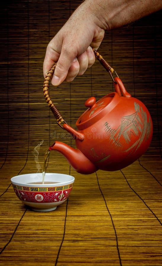 Tè cinese di versamento in una tazza immagini stock