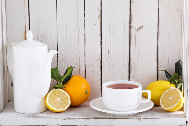 Tè con gli agrumi sullo scaffale fotografia stock libera da diritti
